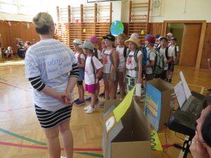 Paní učitelka řadí třeťáky k autobusu